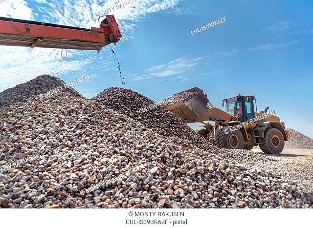 Digger with screened and crushed concrete in concrete recycling site