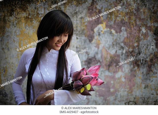 Young woman wearing traditional Vietnamese outfit holding lotus flowers