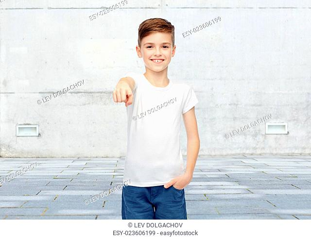 childhood, fashion, advertisement and people concept - happy boy in white t-shirt and jeans pointing finger to you over urban street background