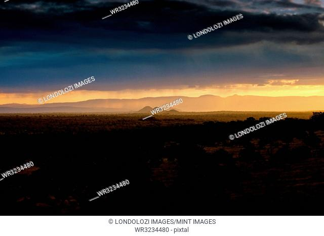 A landscape, dark trees and bushes in foreground, silhouette of mountains in the background, heavy grey clouds, sunset with rain in the background