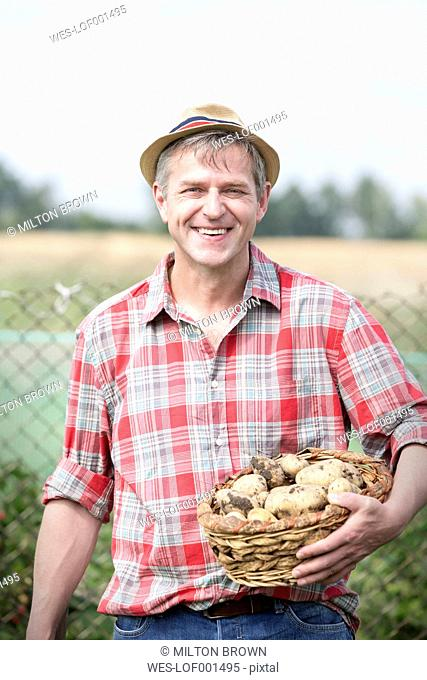 Smiling farmer on organic farm holding basket with potatoes