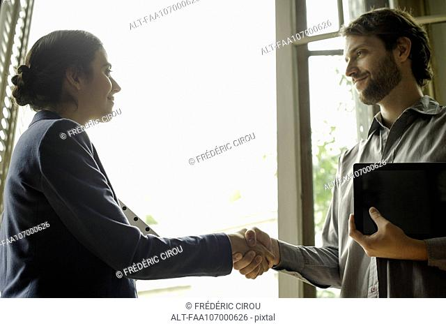 Insurance agent shaking hands with prospective client