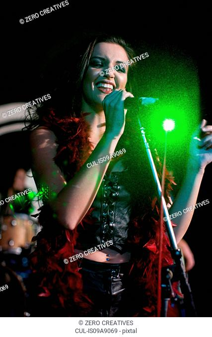 Young female singing on stage in nightclub