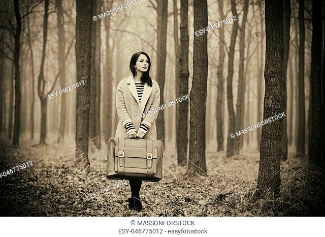 portrait of a young woman with a suitcase standing in the middle of the forest