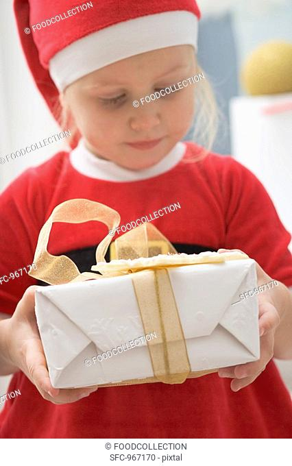 Small girl in Father Christmas costume holding gift