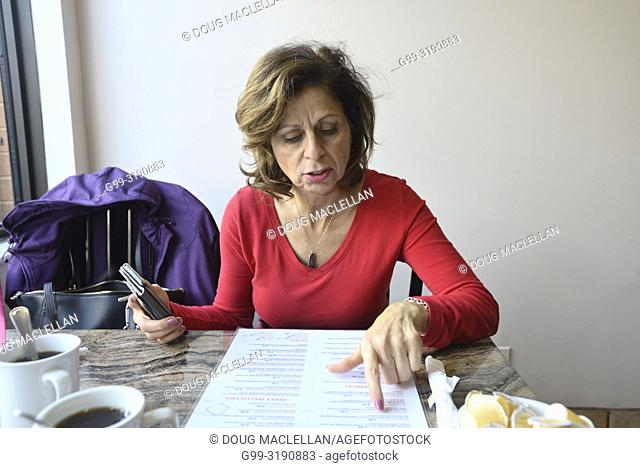 A woman in a red blouse reads a menu in a popular restaurant, Windsor, Canada