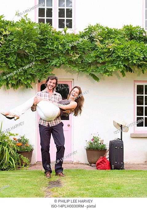 man lifting woman by front of house