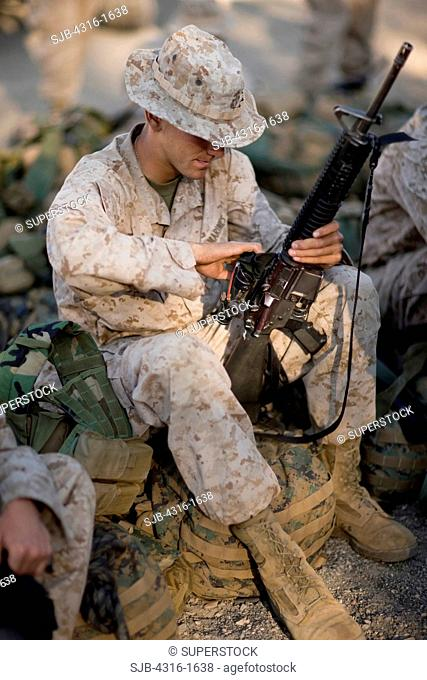 U.S. Marine Maintains His M16 Service Rifle
