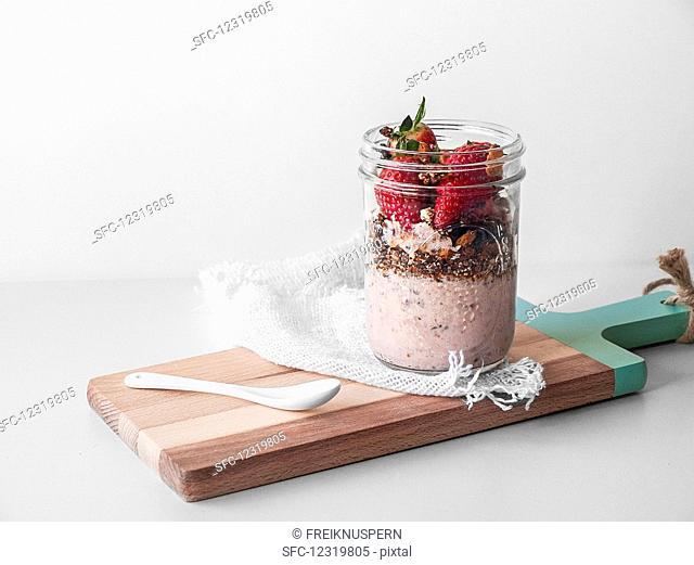 A vegan breakfast in a glass with yoghurt, muesli and strawberries