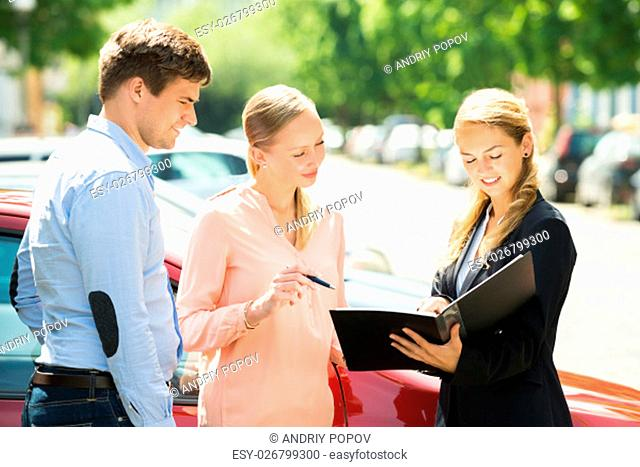 Saleswoman Explaining Contract Paper To Happy Couple Buying A New Car