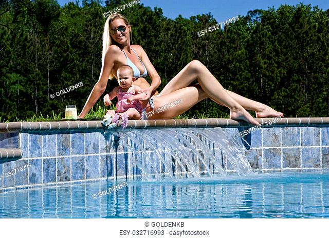 Mother and six month old baby playing by swimming pool