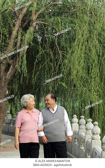 Older couple walking arm and arm in a park