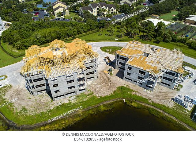 Aerial view of Condominium new home construction showing wood trusses atop on a cement block of 9 individual home units