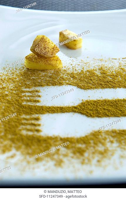Fork prints in curry powder on a plate with curried potatoes