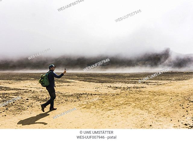 New Zealand, Tongariro National Park, hiker taking a photo with smartphone