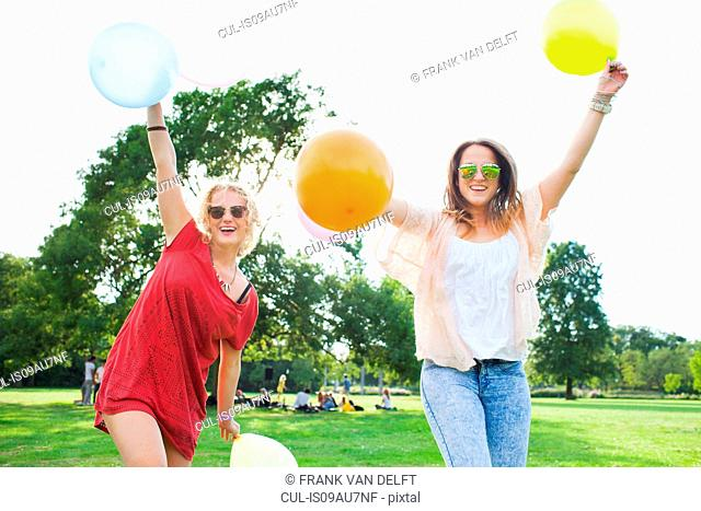 Portrait of two young women dancing with balloons at park party