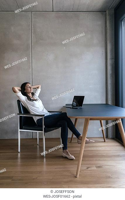 Woman sitting at table with laptop leaning back