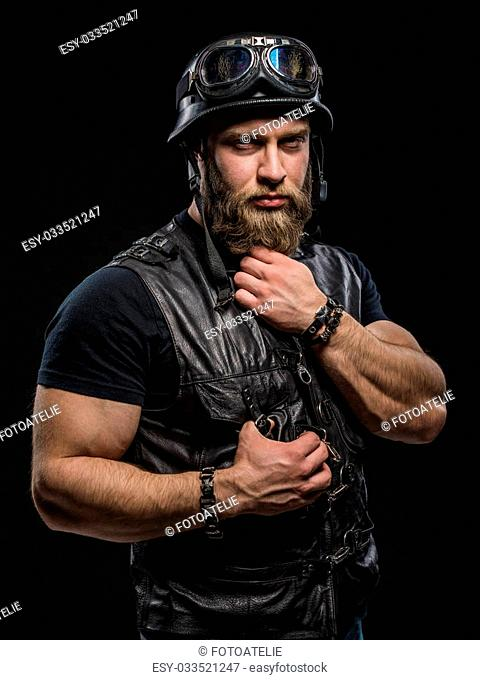 Portrait Handsome Bearded Biker Man in Leather Jacket and Helmet over Black Background