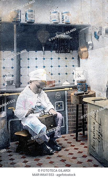 CUCINA in scala ridotta a misura di bambino che recita la parte del cuoco, il piccolo macina il caffè. Fotocollografia acquarellata, Parigi 1902