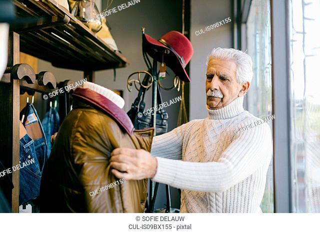 Senior man working in clothes shop