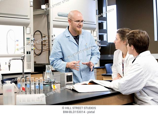 Caucasian teacher and students talking in science lab