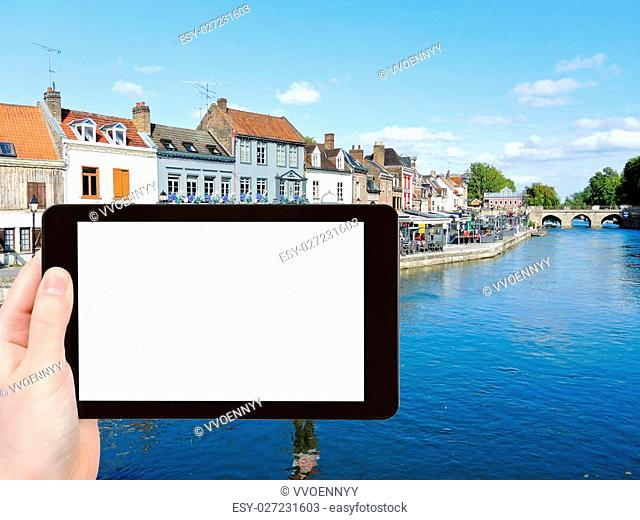 travel concept - tourist photograph Quai Belu on Somme river in Amiens city, France on tablet pc with cut out screen with blank place for advertising logo