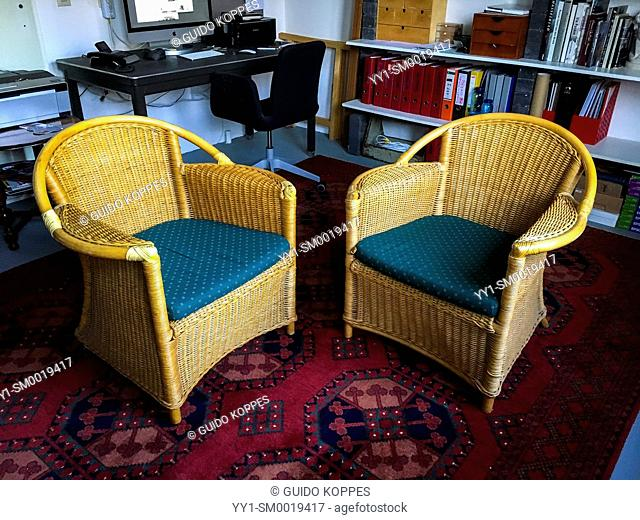 Tilburg, Netherlands. Two rattan of wicker chairs on a red antique carpet inside a studio and office