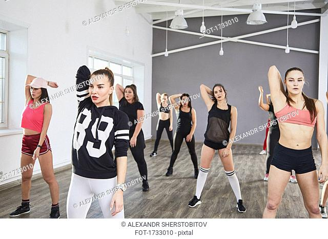 Confident women stretching hands while dancing in studio
