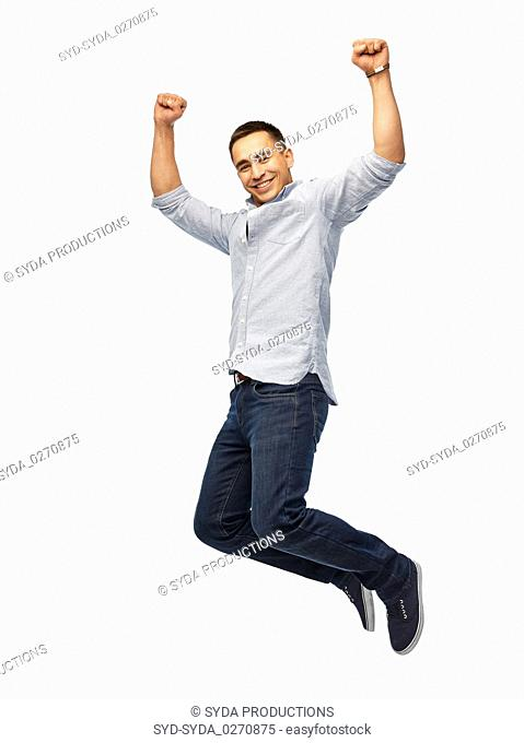 happy young man jumping over white background