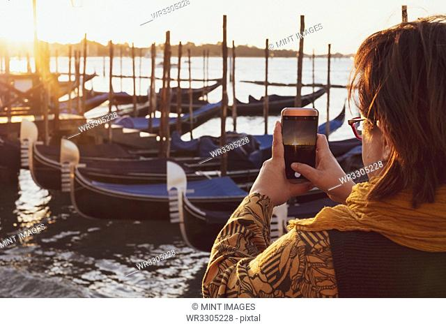 Over the shoulder view of woman taking picture of gondolas moored in the Canale Grande in Venice, Veneto, Italy