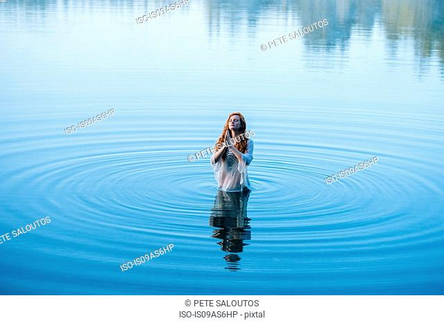 Young woman standing in lake ripples praying with eyes closed