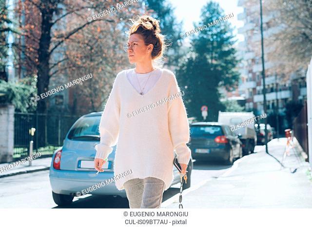 Woman walking on sunny street, Milan, Italy