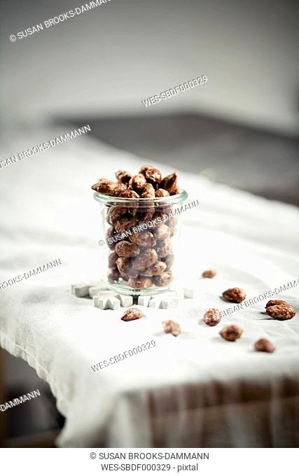 Candied almonds in jar on table