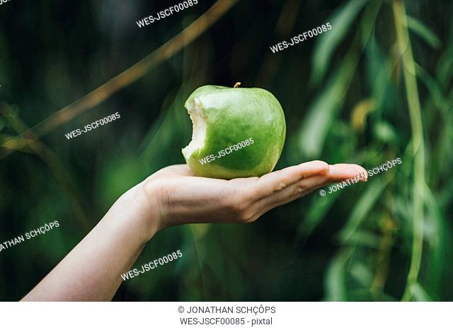 Woman's hand holding bitten apple