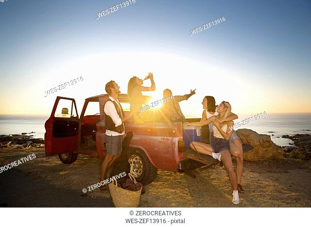Happy young people outside pick up truck at the coast at sunset