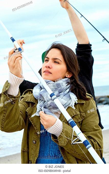Young woman and boyfriend preparing fishing rod line on beach