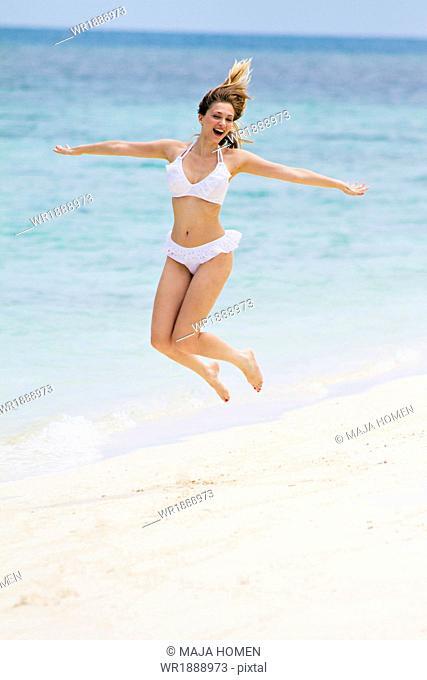 Young woman in bikini jumping on beach, Lankayan Island, Borneo, Malaysia