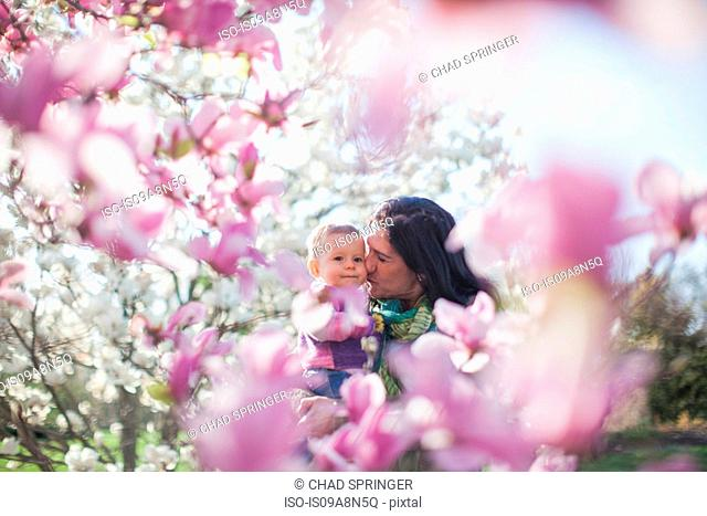 Granddaughter and grandmother amongst magnolia blossom