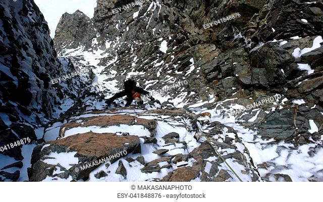 A male mountain climber in a steep rock and ice couloir on his way to a high alpine summit