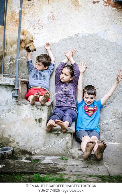 children sitting on the ladder with muddy feet