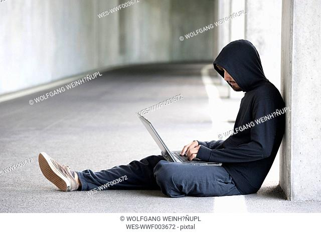 Hacker with laptop sitting in an underground car park