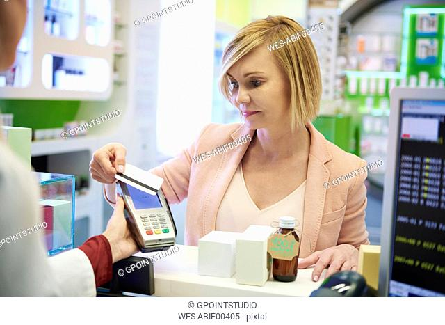 Portrait of woman paying cashless with credit card in a pharmacy
