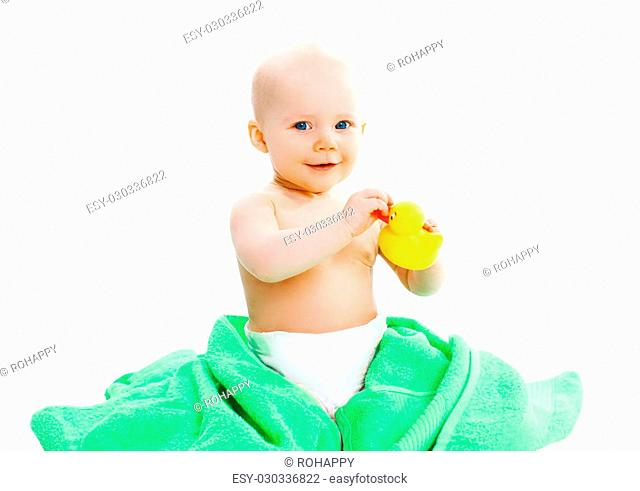 Cute baby playing with yellow rubber duck on the towel