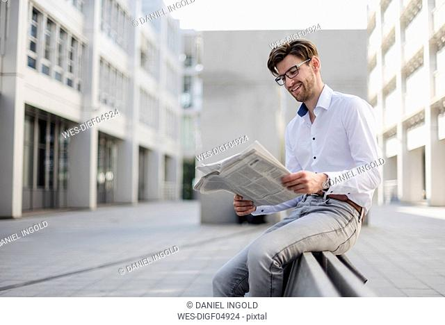 Smiling businessman sitting in the city reading newspaper
