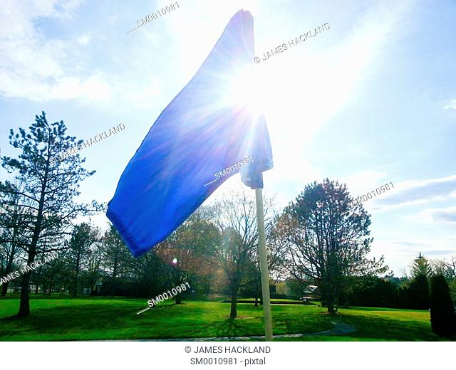 The flag atop the pin on the green of a golf course in Southern Ontario, Canada on a spring day