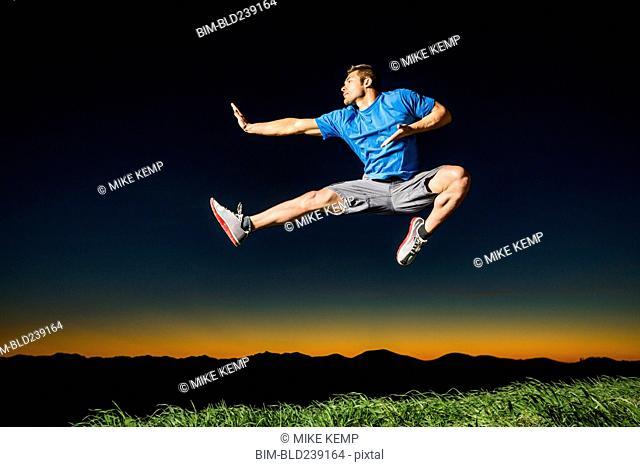 Caucasian man jumping at sunset