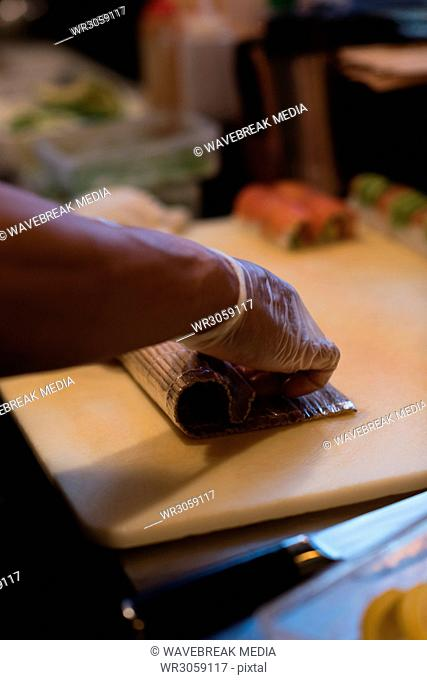 Chef rolling unrolled sushi