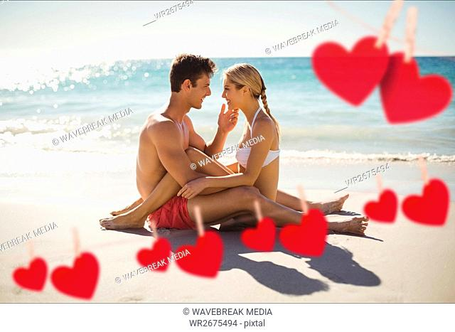 Composite image of red hearts and couple cuddling on beach