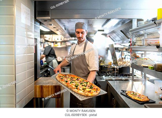 Chef in kitchen holding a Pinsa Romana, a Roman style pizza blend reducing sugar and saturated fat, containing rice and soy with less gluten