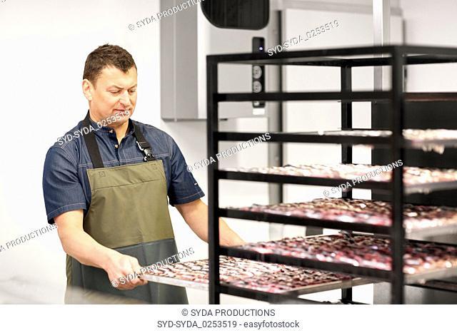 man with smoking tray at fish shop or smokehouse